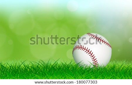 New baseball sitting on lush grass in front of a soft background