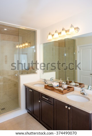 New bathroom. Spacious frame-less glass shower stall. Wood tray contains antique silver hand mirror, limoges porcelain jewelry box. Marble counter top. Double vanity sinks.Interior design ideas.