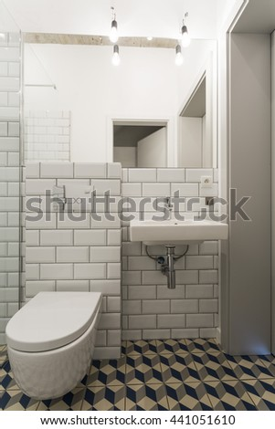 New bathroom with a mirror, basin, toilet and white brick effect tiles - stock photo