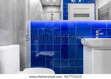 New bathroom with basin cabinet, toilet, shower, mirror and tiling in grey and blue
