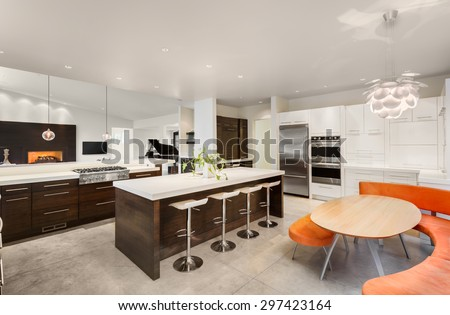 new beautiful furnished kitchen in luxury home with view of living room, including fireplace, and piano  - stock photo