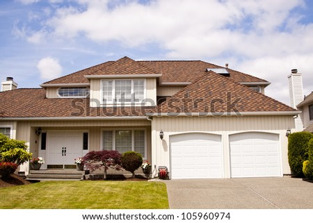new beautiful suburban luxury house at sunny day with green grass - stock photo