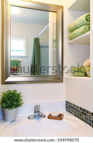 New beautiful white sink with green towels and mirror with white shelves. - stock photo