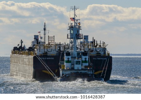 New Bedford, Massachusetts, USA - February 3, 2018: Barge Double Skin 50 being pushed into Buzzards Bay by tug Delaware