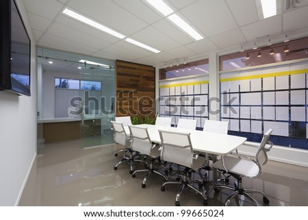 New board room with table, chairs and LCD display on wall. - stock photo