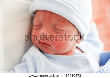 New born baby boy sleeping in the cod just after being born - stock photo