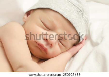 New born baby boy sleeping. Little baby with cute gray hat taking a nap. - stock photo