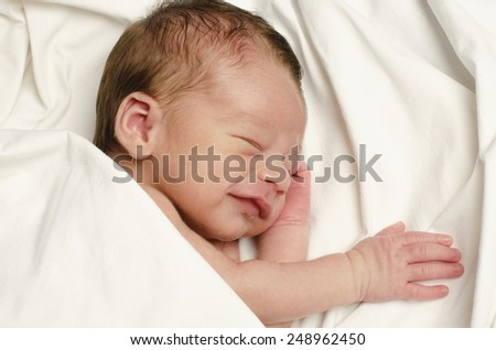 New born baby boy smiling in his sleep. Ten days baby happy laughing during his nap. - stock photo