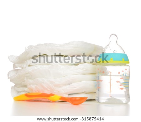 New born baby child stack of diapers spoon baby feeding milk bottle with water on a white background - stock photo