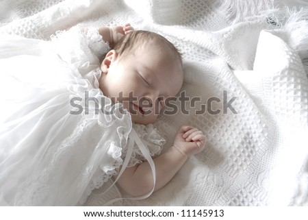 New born baby girl dressed in white asleep on a white blanket - stock photo