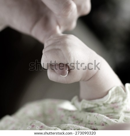 New born baby girl held by her mother - stock photo