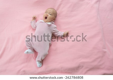 new born baby girl sleeping, yawning on pink background - stock photo