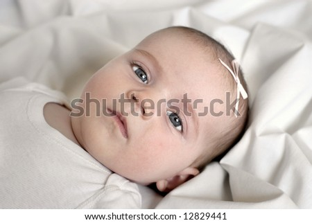 New born baby girl with bow lying on a white blanket