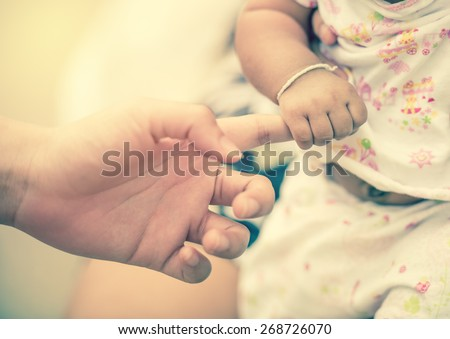 New born baby hand ; vintage tone style - stock photo
