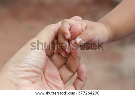 New born baby hand with mother hand - stock photo