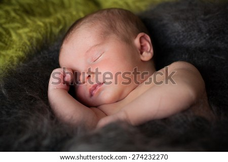 new born baby is sleeping in downy shawl, lying baby, eyes are closed, put out tongue - stock photo