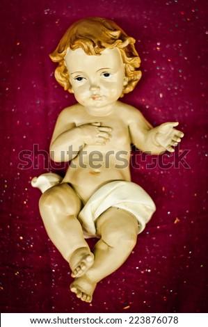 New Born Baby Jesus Christ figure on purple background - stock photo