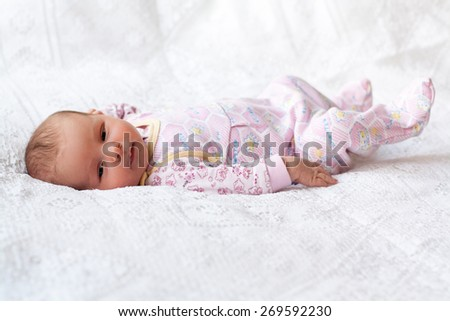 new born baby lying on texture blanket, light pink colors, looking at camera - stock photo