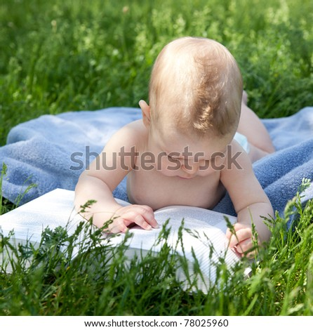 New born baby read book in park - stock photo