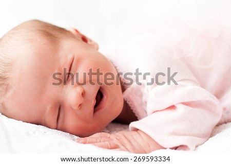 new born baby sleeping on texture blanket, lying on blanket, closed eyes, light pink dress - stock photo