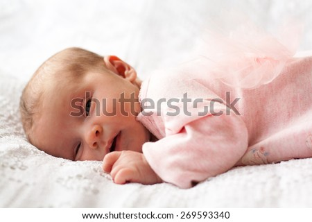 new born baby sleeping on texture blanket, lying on blanket, light pink dress with bow-knot on back - stock photo