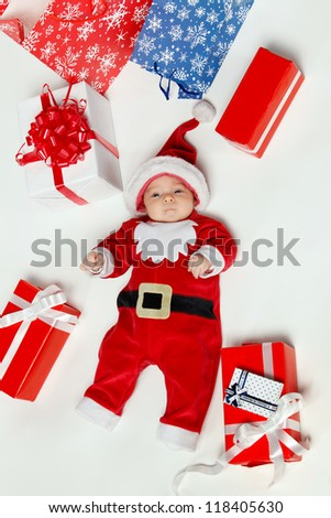 New born baby wearing Santa Claus costume surrounded by Xmas gifts, over white background - stock photo