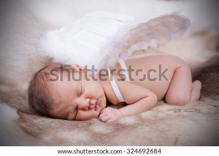 New born baby wearing white angel wings. - stock photo