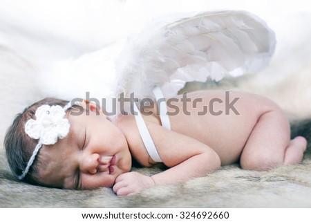 New born baby wearing white angel wings and white headband. - stock photo