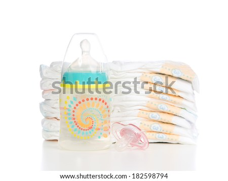 New born child stack of diapers, nipple soother baby feeding bottle with water on a white background - stock photo