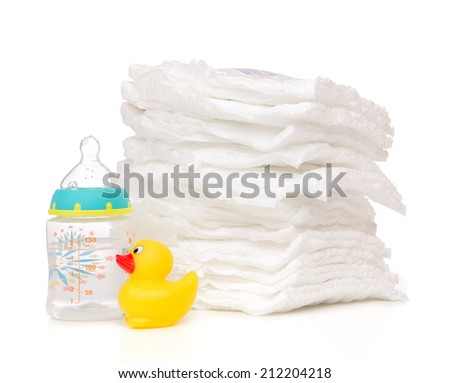 New born child stack of diapers nipple soother baby feeding milk bottle with water and yellow duck on a white background - stock photo