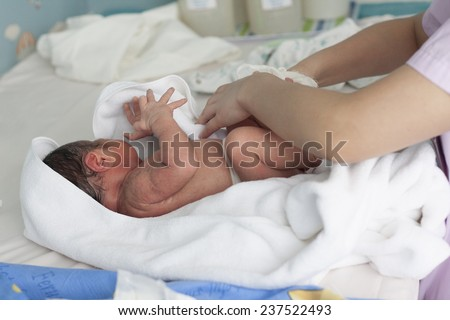 new born infant in nurse hand