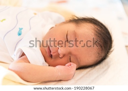 New born male Thai baby in various sleeping action, taken without flash