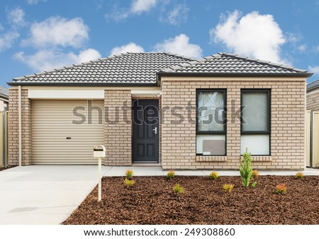 new brick house with garage and plants - stock photo
