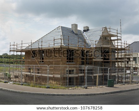 new build home surrounded by fencing and scaffolding - stock photo