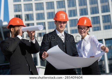 New building project. A group of three architects are looking forward while standing on the street in construction helmets and holding blueprints in hand. Business architects concept