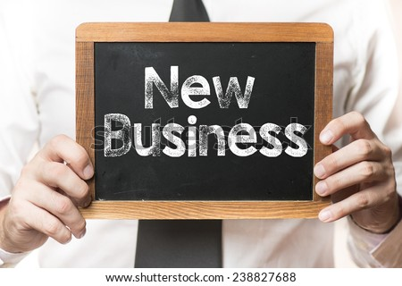 New business Background. New business Background . Businessman holding board on the background with new business words
