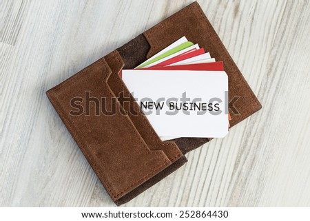 """New business. Conceptual composition with leather business-card folder, stack of colorful business cards and white business card with phrase """"New Business"""" on the foreground. - stock photo"""