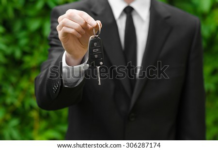 New car and business theme: a man in a black suit holds the keys of a new car on a background of green grass - stock photo
