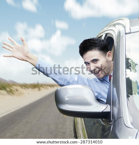 New car owner driving the car on the road while waving hand through the window