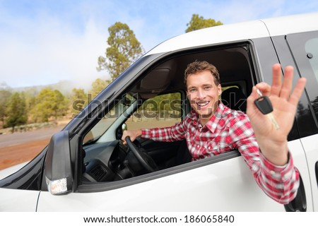 New cars - man driving car showing car keys happy looking at camera. Male driver on road trip in beautiful landscape nature. Focus on model. - stock photo