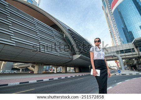 New cases. Successful arabic businesswoman standing in the street in formal attire. Businessman standing near skyscrapers in Dubai downtown in sunglasses holding a tablet - stock photo