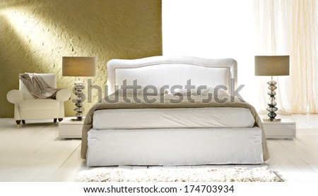 new classic bed in gold colored bedroom - stock photo