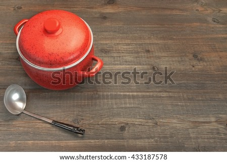 New, Clean Covered Red Saucepan And Ladle On The Rough Rustic Brown Wood Table Background, Overhead View, Copy Space - stock photo