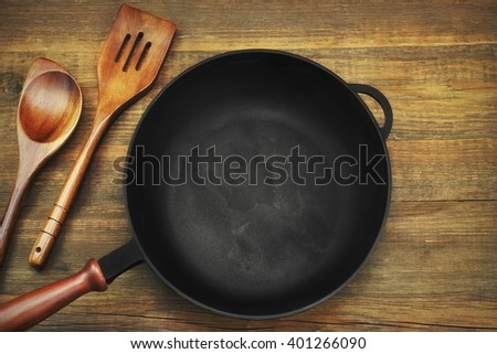 New Clean Empty Cast Iron Frying Pan And Spatula Top View On The Wooden Background - stock photo