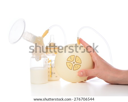 New compact electric breast pump to increase milk supply for breastfeeding mother and bags of frozen breastmilk isolated on white background - stock photo