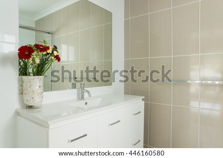 New compact ensuite bathroom with tiled walls and vanity - stock photo