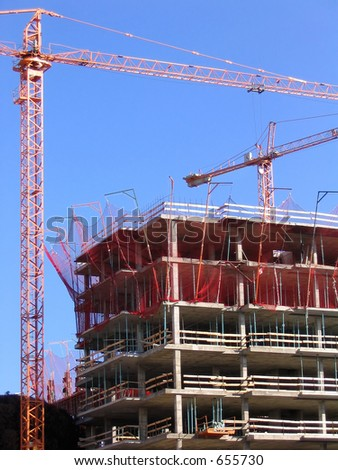 New construction building, blue sky and cranes