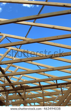 New construction home framing against blue sky vertical image