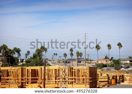 new construction in framing stage with palm trees in background