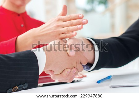 New contract. Three successful and confident businesspeople shake hands. Businesspeople in formal dress sitting in an office at a desk and smiling at the camera - stock photo